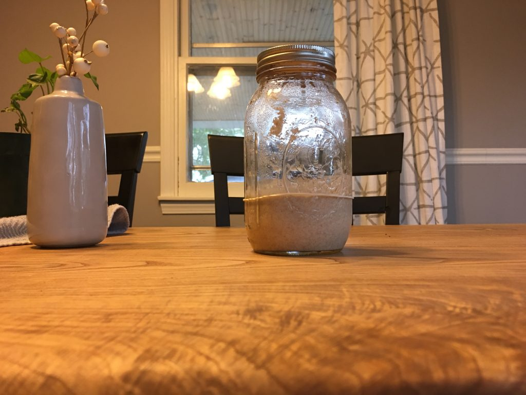 A narrow mouth mason jar sits on a wood table with its metal lid attached. The outside lighting is dim so the dining room light is turned on to show the starter inside the jar.