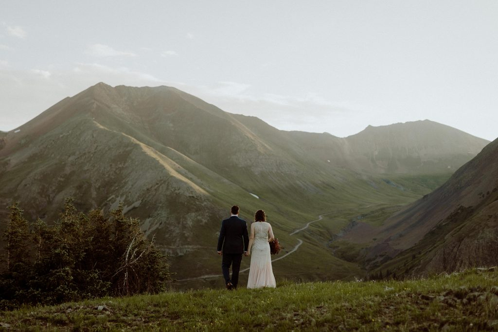 My wife and I on our wedding day standing on a hill overlooking a mountain range at sunrise in Colorado